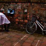 Un barbiere che lavora su un cliente seduto per strada. Situazione molto improvvisata