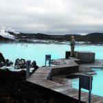 Laguna blu, pozza d'acqua calda color turchese con passerella di legno per camminarci sopra e in lontananza i fumi della centrale grotermica
