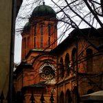 Particolare architettonico di un monastero romeno in mattoni rossi. Presenta due cupole bizantine che si intravedono tra i rami degli alberi spogli