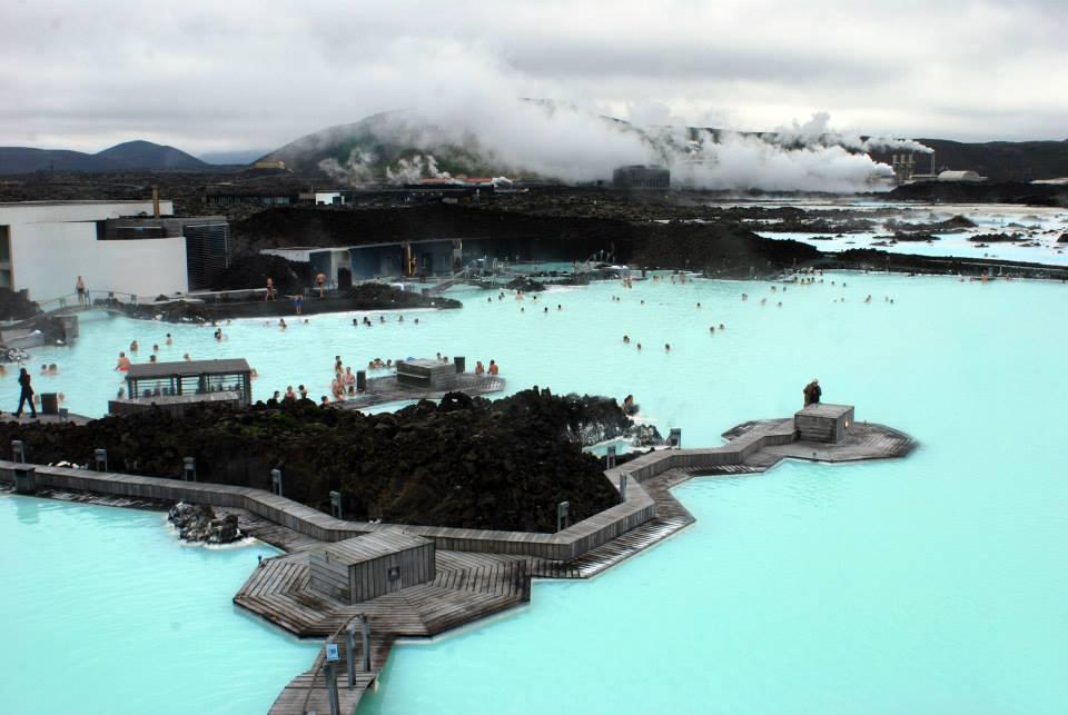 Terme all'aria aperta: una enorme piscina naturale color turchese con passerelle e centri per il ristoro. In lontananza si vedono i fumi della centrale grotermica