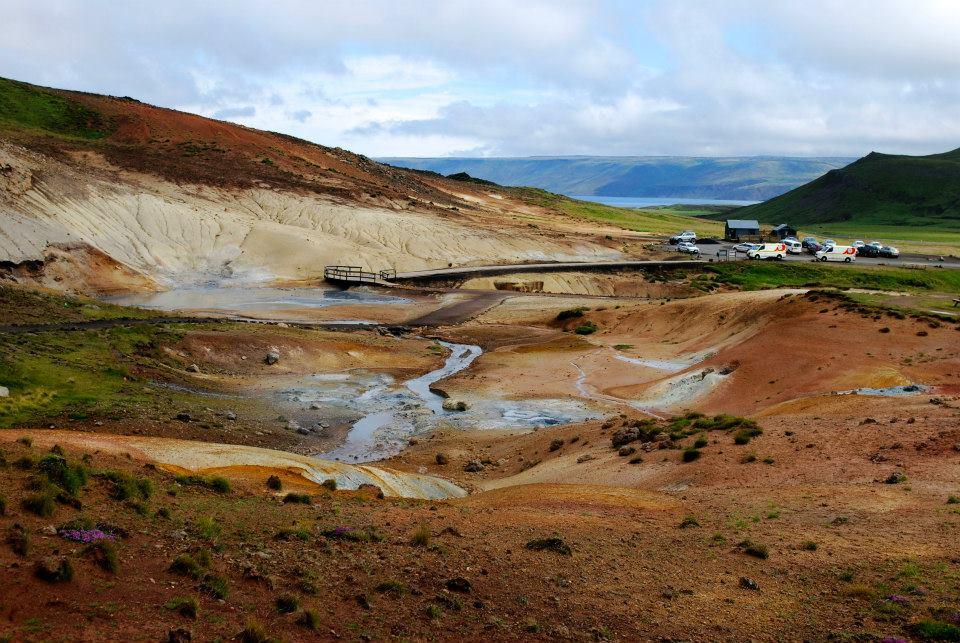 Solfatare in Islanda. Terra dal colore rosso, fiumiciattoli fumanti, lago in lontananza
