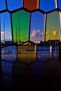 Vetrate colorate di forma irregolare che si riflettono sul pavimento lucido e dalle quali si vede il porto con le barche a vela, il mare e le nuvole