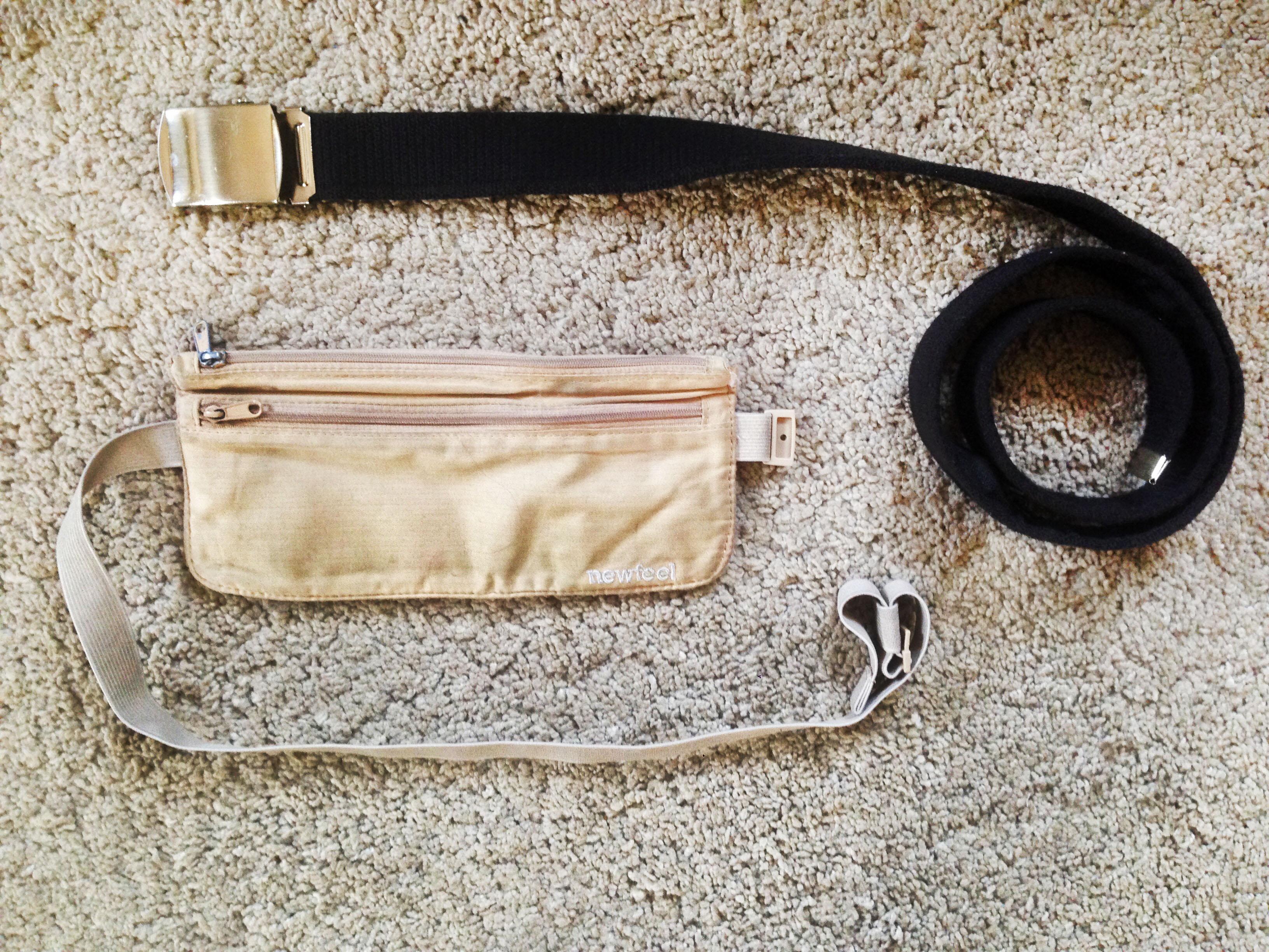 Un marsupio color crema e una cinta nera di stoffa appoggiate su un tappeto bianco a tinta unita
