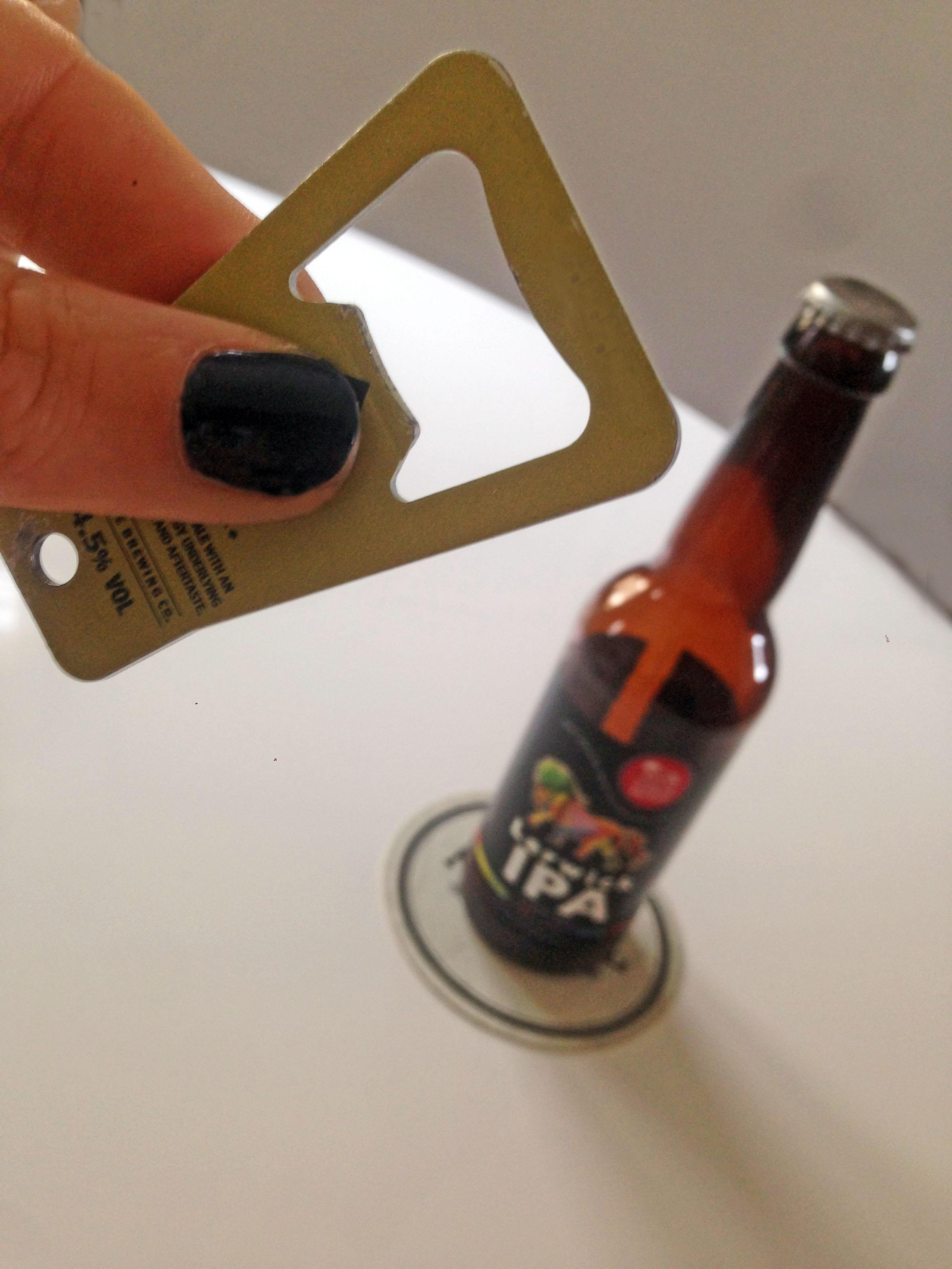 Uno stappa bottiglie e una birra in bottiglia su un tavolo